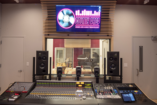 The Studio at County Prep High School in New Jersey installed at the front of a teaching space with seating for about 16 students -- it overlooks a tracking room with a piano and two soundproof booths.